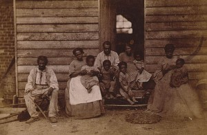 Slave family or families posed in front of wooden house in DC or Hampton, VA, 1861. [Library of Congress]